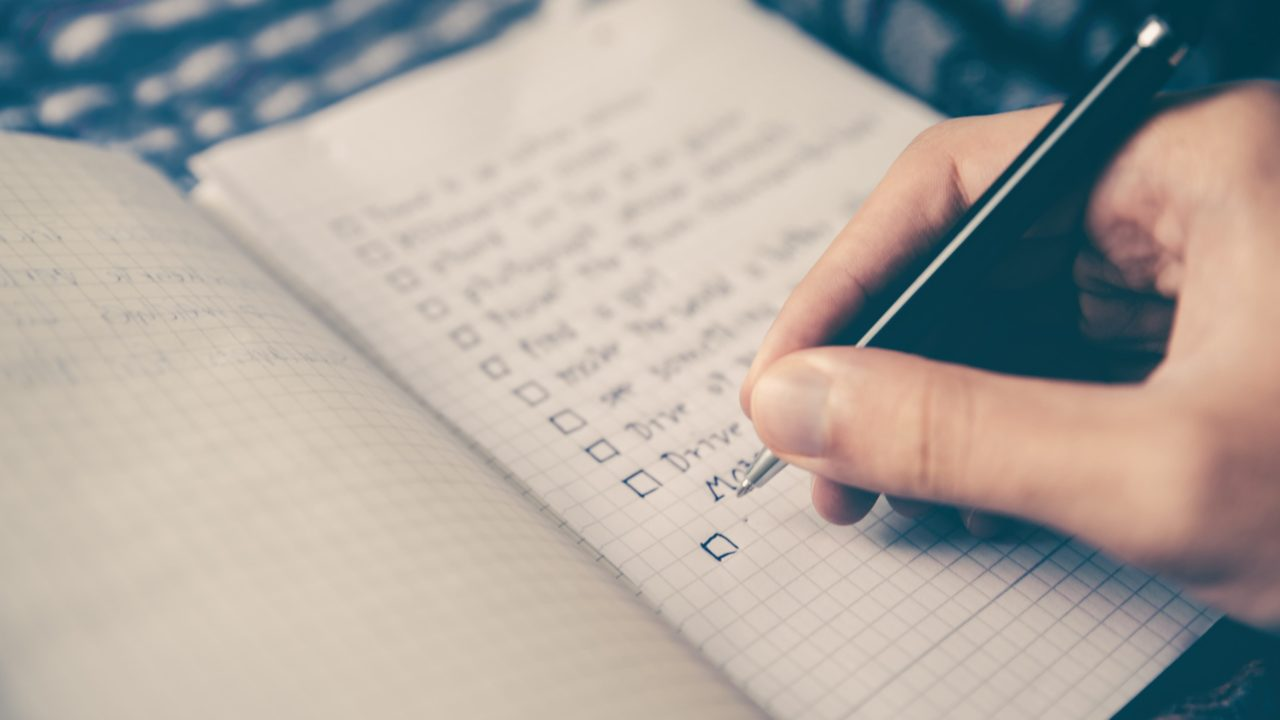 ノートにペンでリストを書き込んでいる