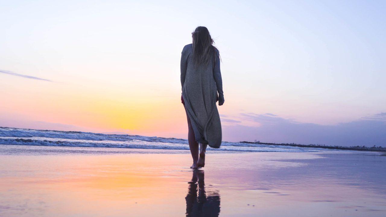 浜辺を歩く女性の後ろ姿