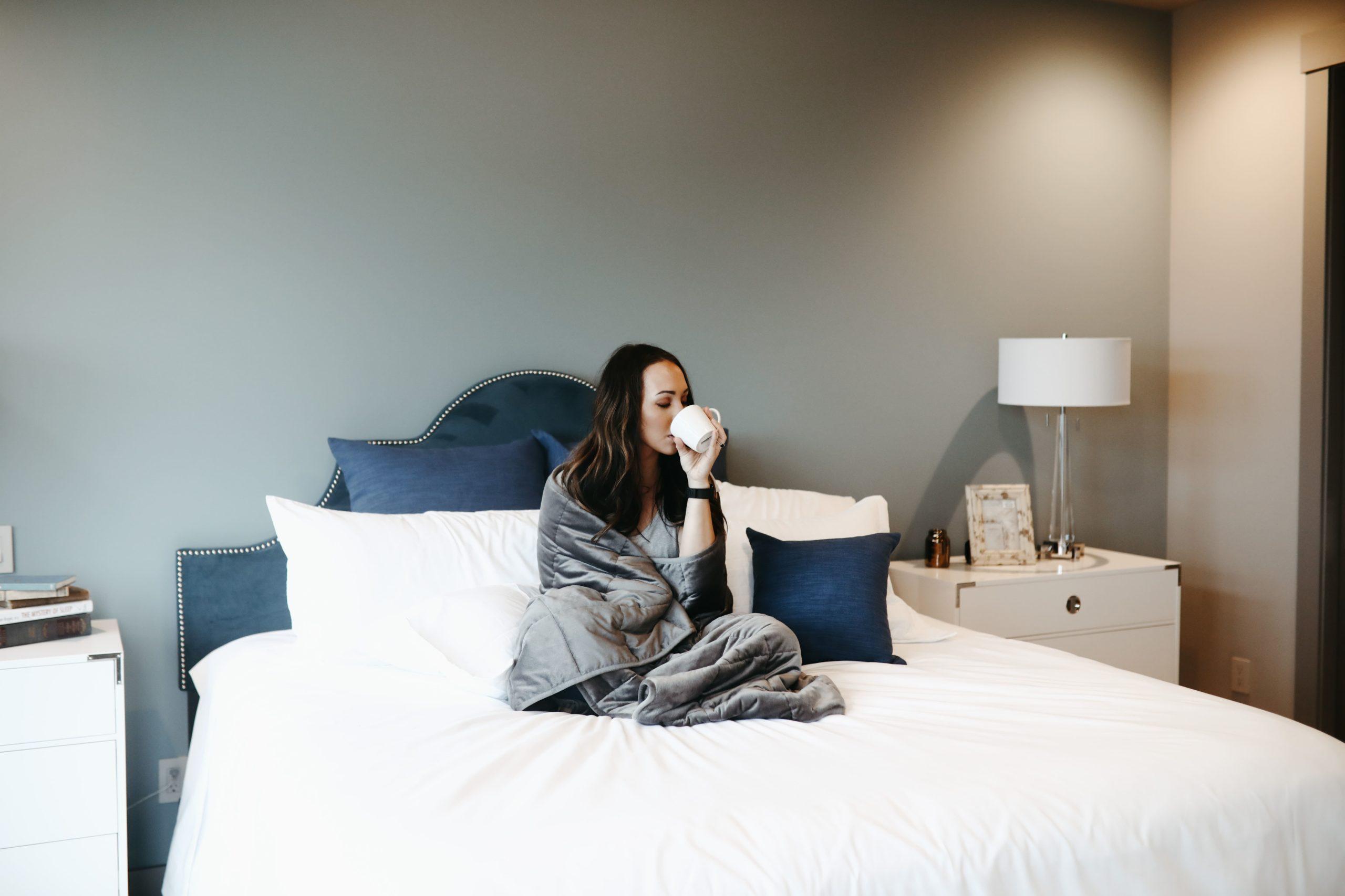 ベッドの上でコーヒーを飲む女性