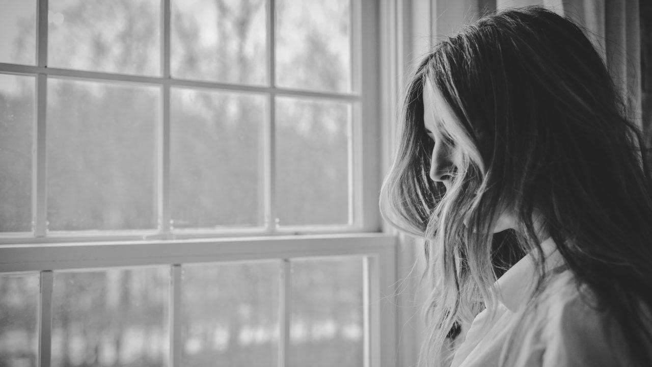 落ち込みながら窓を眺める女性