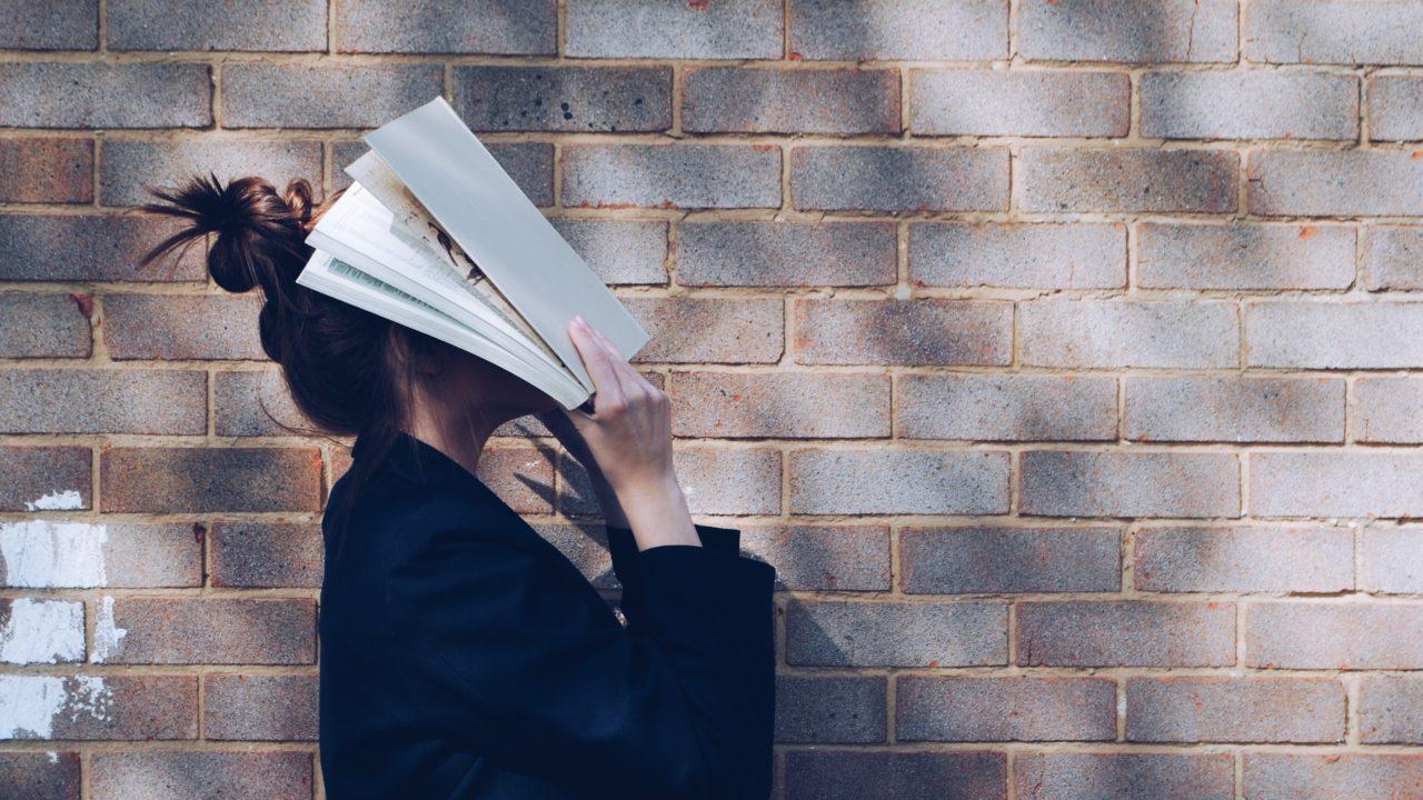 本で顔をおおう女性