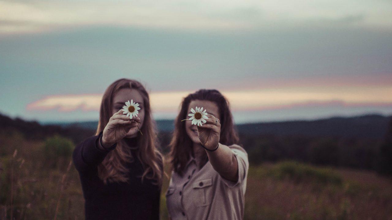 花を持って笑うふたりの女性