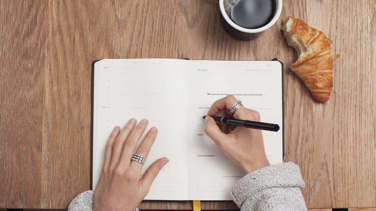 手帳に予定を書いている女性の手