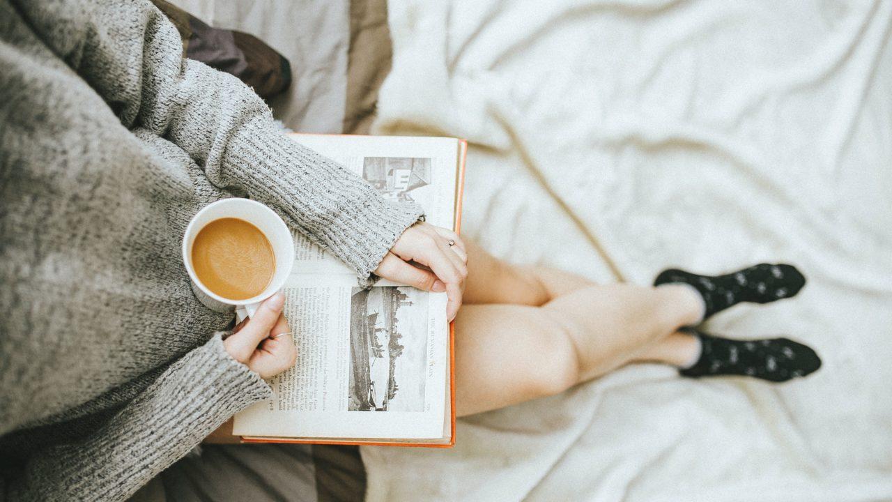 ベッドの上でコーヒーと本を手にした女性