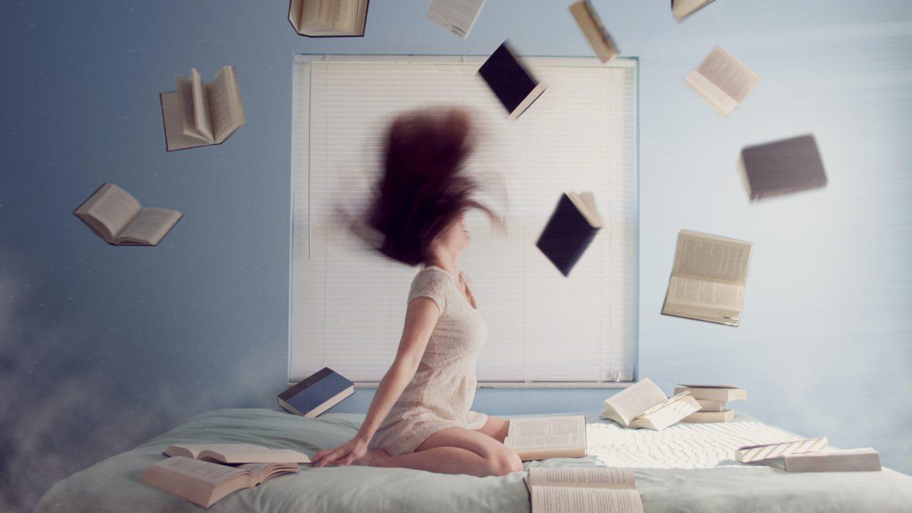 髪を振り乱して本を吹き飛ばす女性