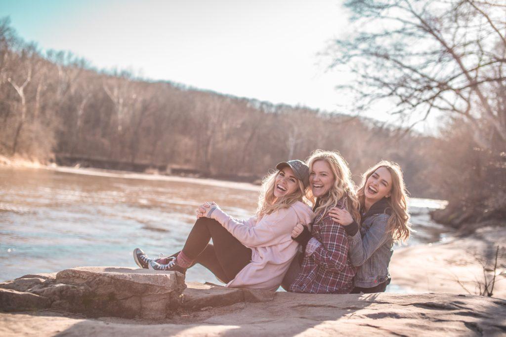 川沿いではしゃぐ女性3人