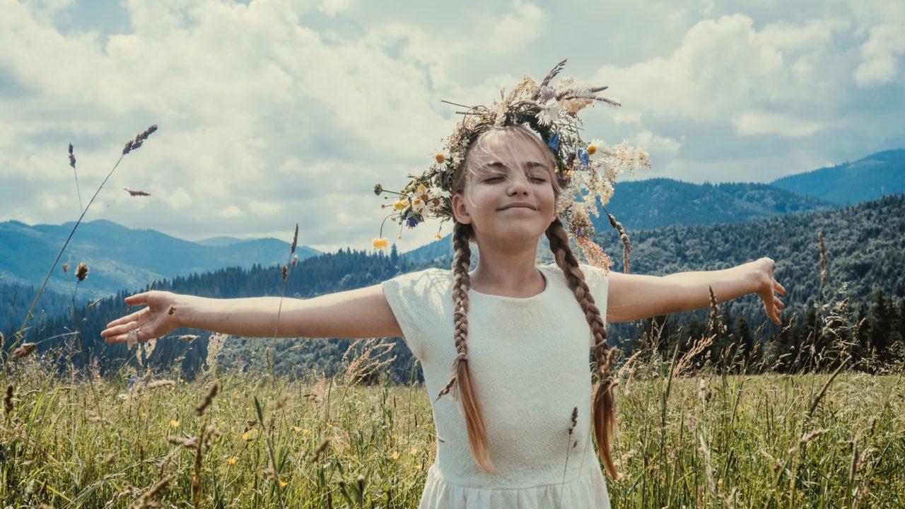 草原で手を広げている女の子