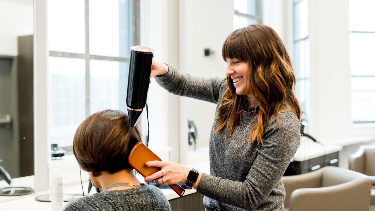 美容院でドライヤーをしてもらっている女性