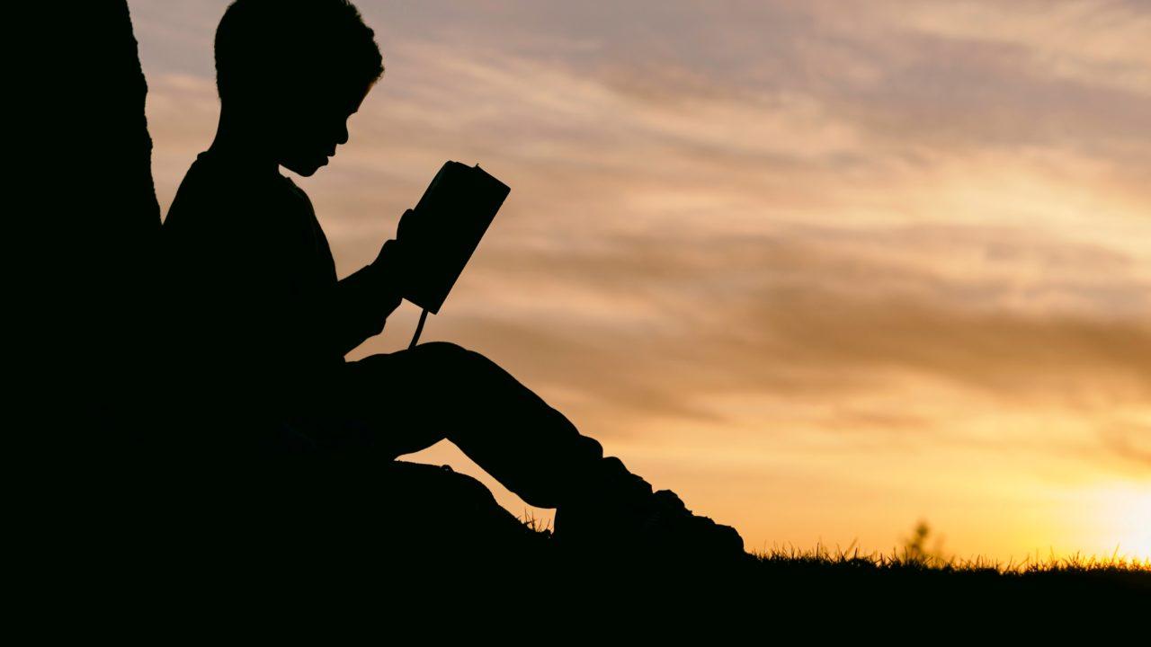 夕焼けを背景に本を読む少年