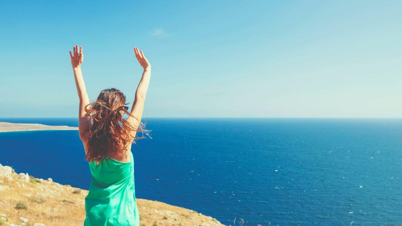 海を向いて伸びをする女性