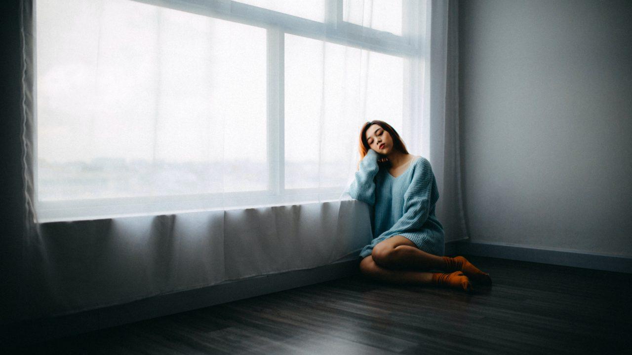 部屋の隅に一人で座る女性